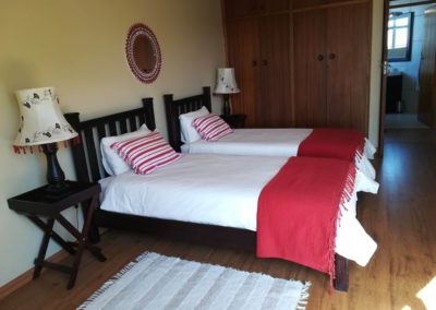 The two single beds and cupboards inside the third upstairs bedroom